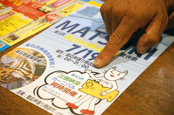 ポスターを指さす会長