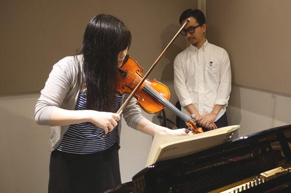 バイオリンの調弦をする先生、小さく固まる編集長